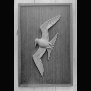 Tern in flight Lime on teak background in relief